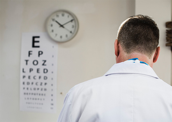 doctor standing by eye chart