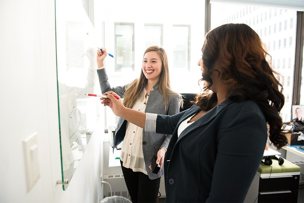 two female employees talking at a whiteboard