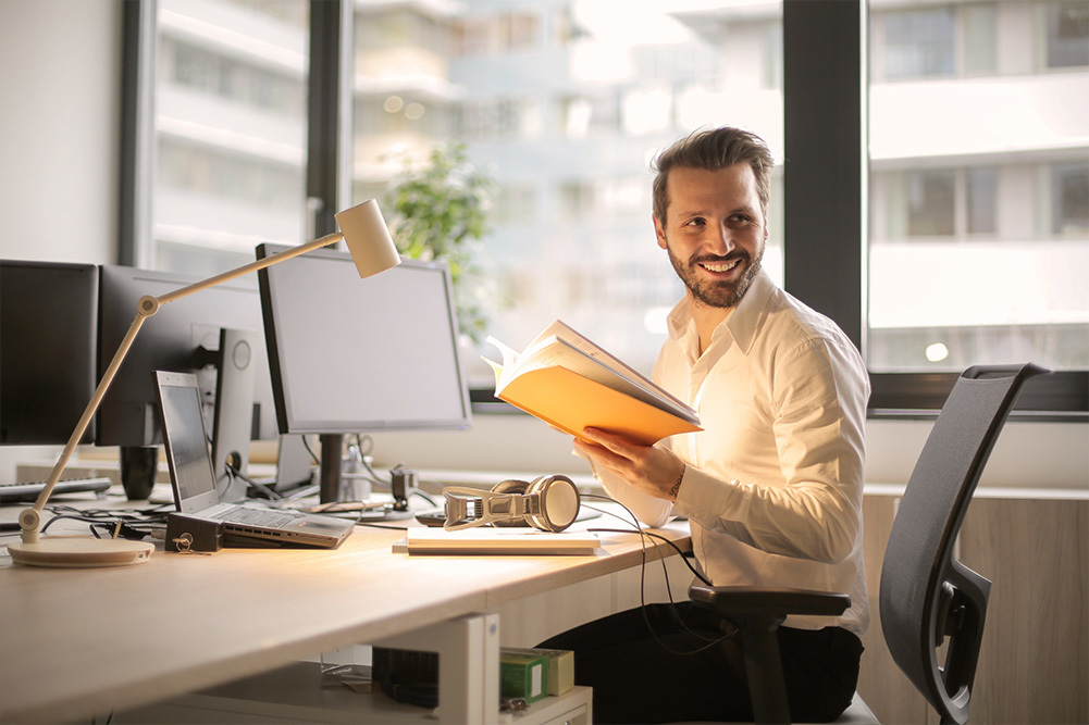 smiling employee working at his desk