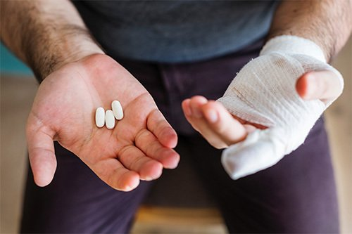 man with bandaged hand holding white pills