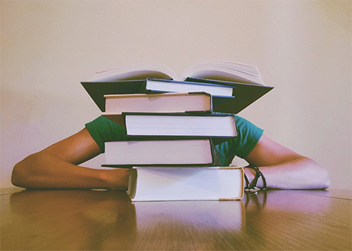 student hiding behind pile of books