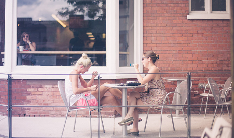 women talking outside at table